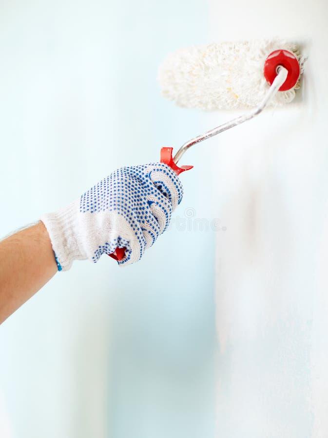 Sluit omhoog van mannetje die in handschoenen muur schilderen royalty-vrije stock fotografie