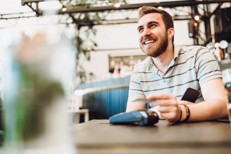 Sluit omhoog van mannetje gebruikend creditcardtechnologie zonder contact en smartphone voor het betalen in restaurant stock foto