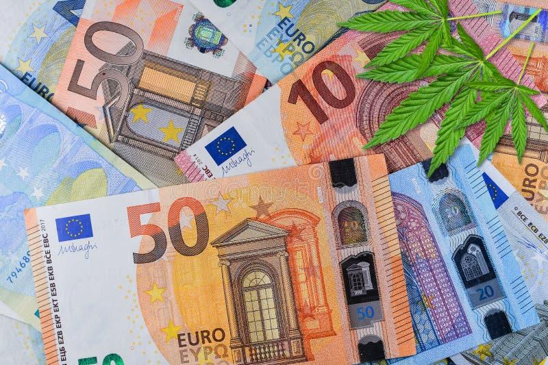 Sluit omhoog van Marihuana op geld Cannabis of hennepbladeren op een euro geldachtergrond Vlak leg Malplaatje of spot omhoog stock afbeeldingen
