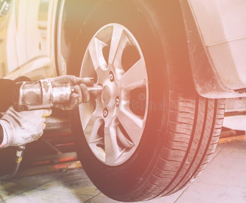 Sluit omhoog van mechanische handen met het pneumatische wiel van moersleutelveranderingen op auto royalty-vrije stock afbeelding
