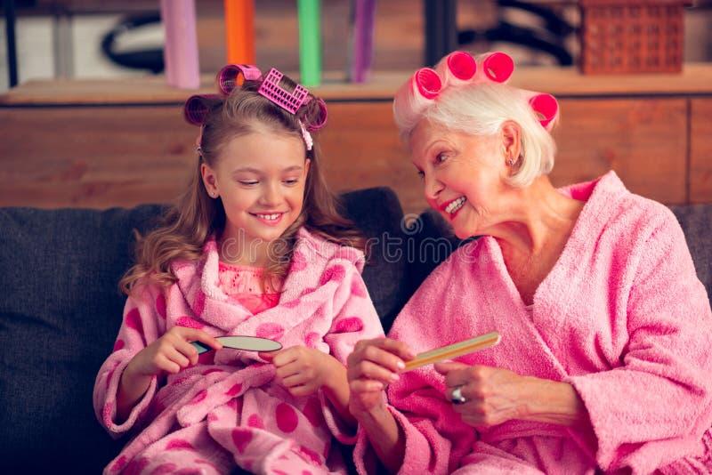 Sluit omhoog van meisje blij voelen terwijl het doen van manicure met oma stock foto's