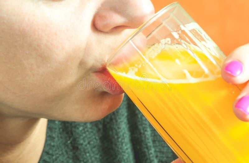 Sluit omhoog van meisjesgezicht en lippen drinkend jus d'orange van het glas als verfrissing, echte mensen, selectieve nadruk stock foto's