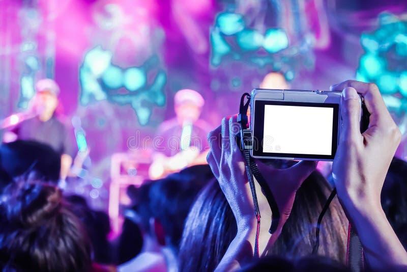 Sluit omhoog van mensen die hun compacte camera houden en een video op een compacte camera vangen bij een muziekfestival stock foto