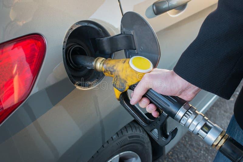 Sluit omhoog van mensen pompende brandstof in auto bij benzinestation stock afbeelding