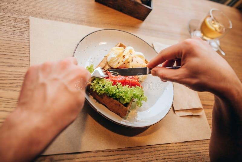 Sluit omhoog van mensen` s handen houdend vork en knofe en het snijden schotel in twee stukken Er is een kop thee op rechterkant stock afbeelding