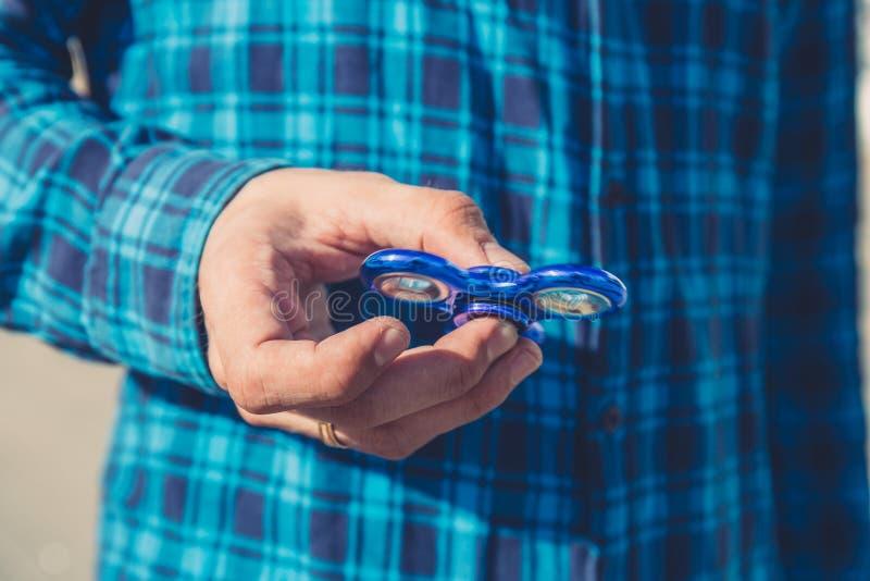 Sluit omhoog van mensenhand het spelen met Fidget Spinner stock afbeeldingen