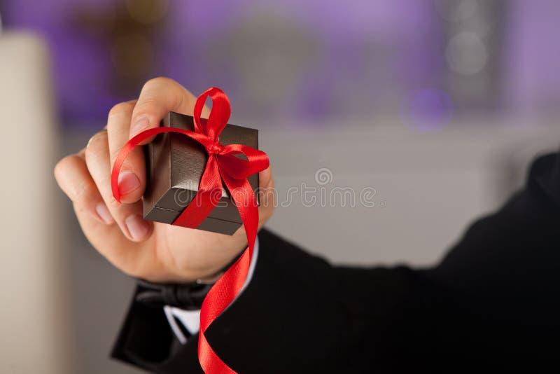 Sluit omhoog van mensenhand houdend kleine gift met lint royalty-vrije stock foto's