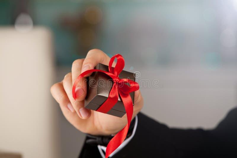 Sluit omhoog van mensenhand houdend kleine gift met lint royalty-vrije stock foto