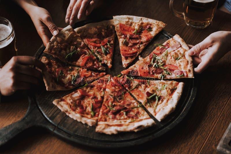 Sluit omhoog van Mensenhanden die Plakken van Pizza nemen royalty-vrije stock foto