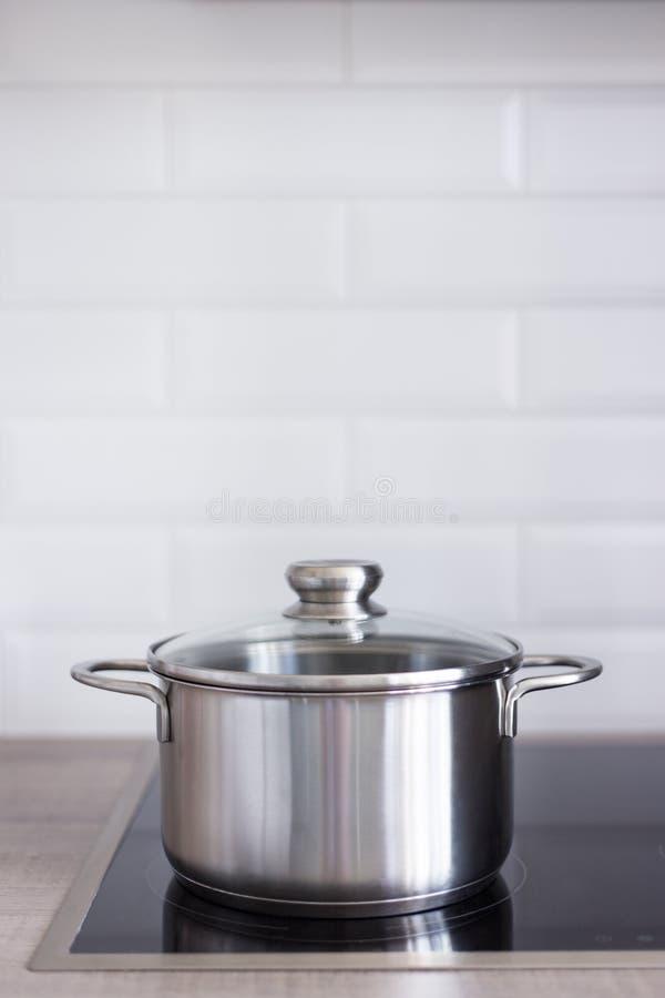 Sluit omhoog van metaalpot op elektrisch fornuis in keuken stock fotografie