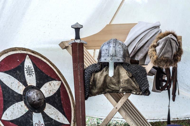 Sluit omhoog van middeleeuws riddermateriaal in oude slaaptent Metaalhelm, schild, zwaard stock afbeelding