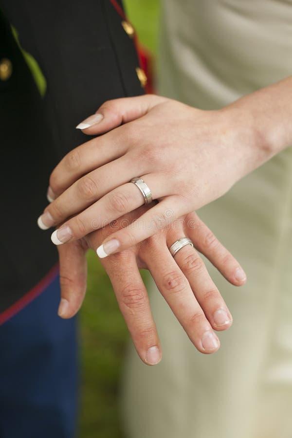 Sluit omhoog van militaire bruidegom en van de bruid trouwringen stock foto