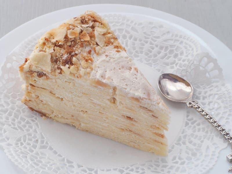 Sluit omhoog van mille feuille op witte plaat met grappige lepel in een vorm van schip Multi gelaagde cake royalty-vrije stock afbeelding