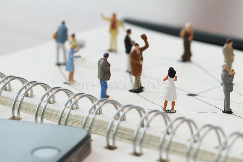 sluit omhoog van miniatuurmensen met sociaal netwerkdiagram op open royalty-vrije stock afbeelding