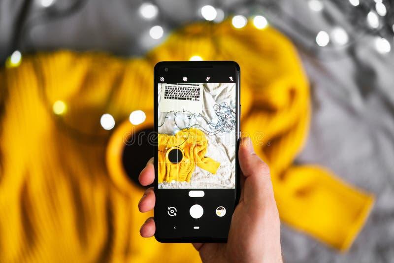 Sluit omhoog van mobiele telefoon makend foto's van sweater en kop thee royalty-vrije stock afbeeldingen
