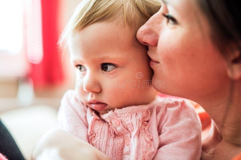 Sluit omhoog van moeder die haar leuke babydochter houden royalty-vrije stock foto