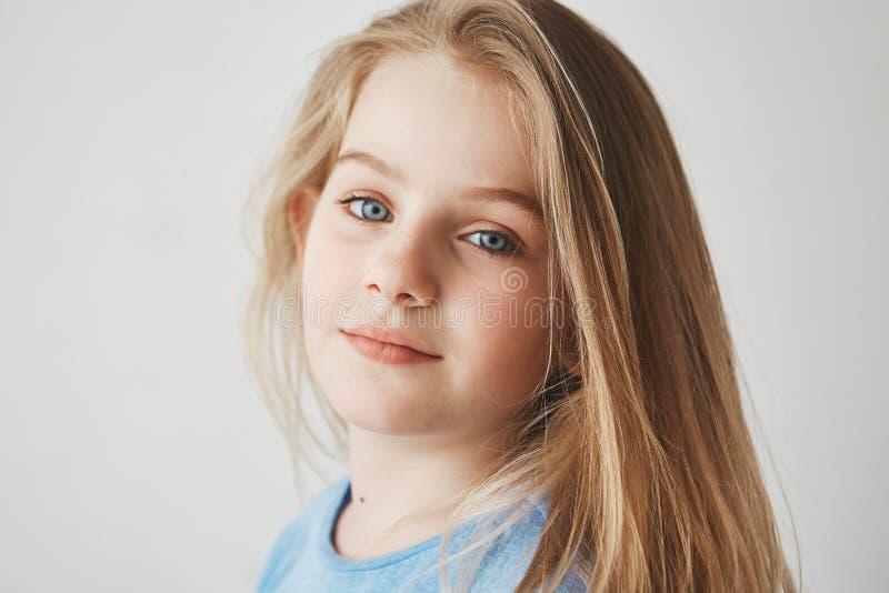 Sluit omhoog van mooi blondemeisje die met heldere blauwe ogen hoofd in drie houden - kwarten, die voor foto met zacht stellen royalty-vrije stock foto