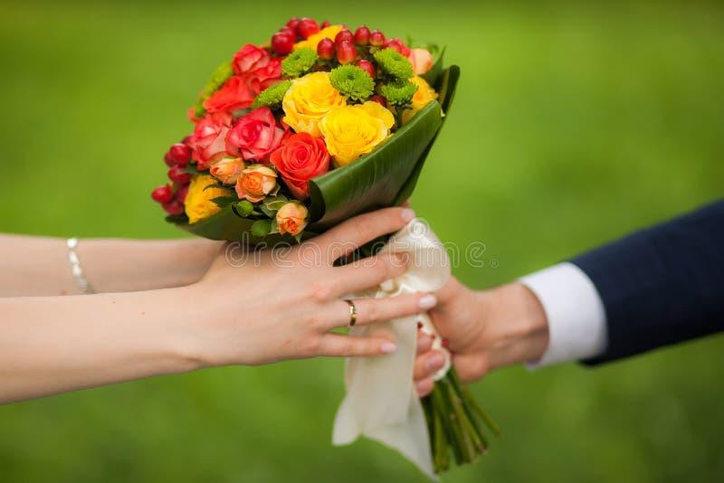 Sluit omhoog van mooi boeket van verse bloemen De handen van de man en van de vrouw gelukkige bruid, bruidegom over achtergrond v royalty-vrije stock fotografie