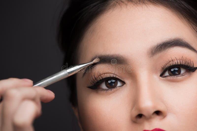 Sluit omhoog van mooi gezicht van jonge Aziatische vrouw die samenstelling krijgen royalty-vrije stock afbeelding