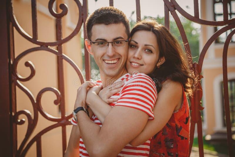 Sluit omhoog van mooi jong glimlachend paar in liefde, koesteren, die achter elkaar zich in openlucht bij stadsstraat bevinden he stock foto's