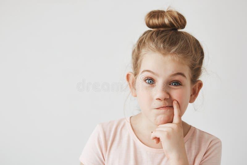 Sluit omhoog van mooi meisje die met blond haar in de holdingsvinger van het broodjeskapsel dichtbij mond, grappige gezichtsuitdr royalty-vrije stock foto