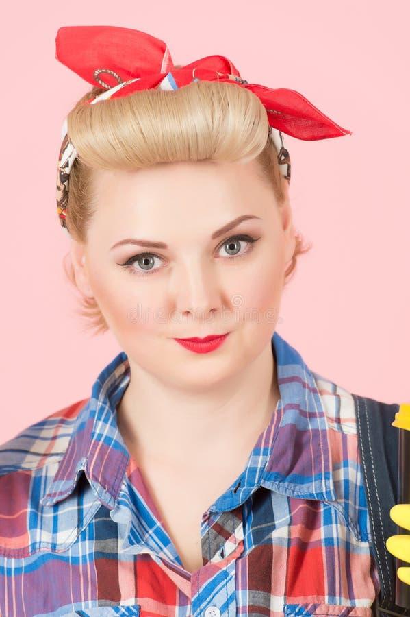 Sluit omhoog van mooie blondevrouw in speld-omhooggaande stijl op roze achtergrond royalty-vrije stock afbeeldingen