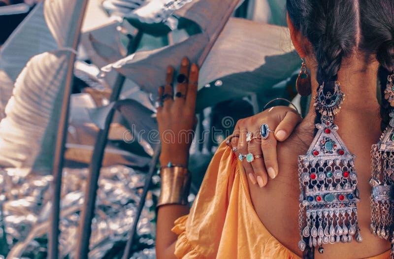 Sluit omhoog van mooie jonge modieuze vrouw met modieuze bohotoebehoren die op natuurlijke tropische achtergrond stellen stock foto
