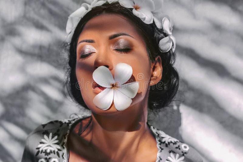 Sluit omhoog van mooie jonge vrouw die kroon dragen en frangipanibloemen houden dichtbij gezicht bij witte achtergrond royalty-vrije stock fotografie
