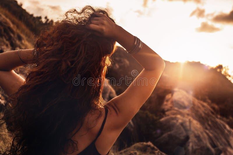 Sluit omhoog van mooie jonge vrouw die in stralen zon plaatsen royalty-vrije stock foto's