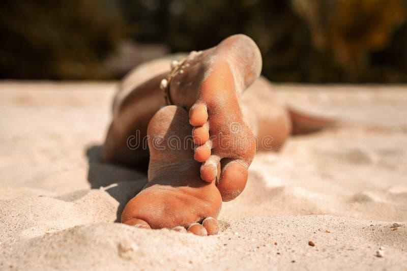 Sluit omhoog van mooie jonge vrouwenvoeten zonbad op het strand royalty-vrije stock fotografie