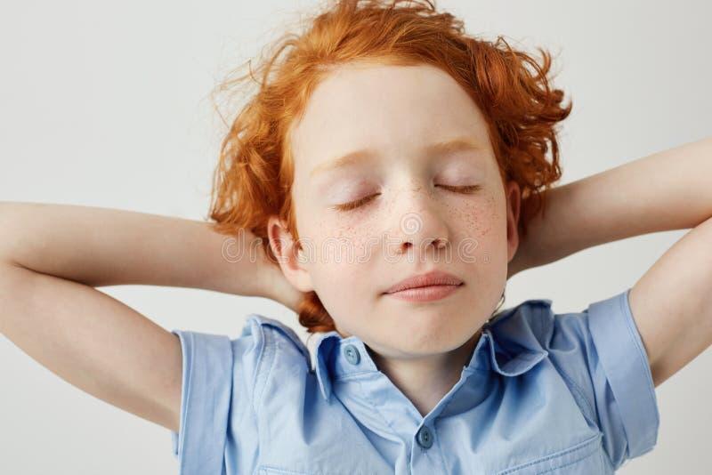 Sluit omhoog van mooie slaperige gemberjongen met krullend haar en sproeten houdend handen achter hoofd met gesloten ogen die zij royalty-vrije stock afbeeldingen
