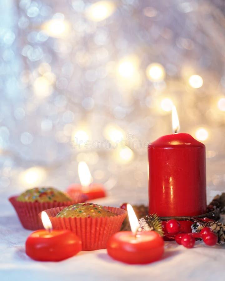 Sluit omhoog van muffins in een rode omslag met rode kaarsen en vakantiekroon Bokehachtergrond met een ondiepe diepte van gebied royalty-vrije stock fotografie
