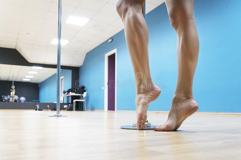 Sluit omhoog van naakte gespierde benen van poledancer het stellen vóór poledance bij discoachtergrond De sterke benen die van he stock foto's