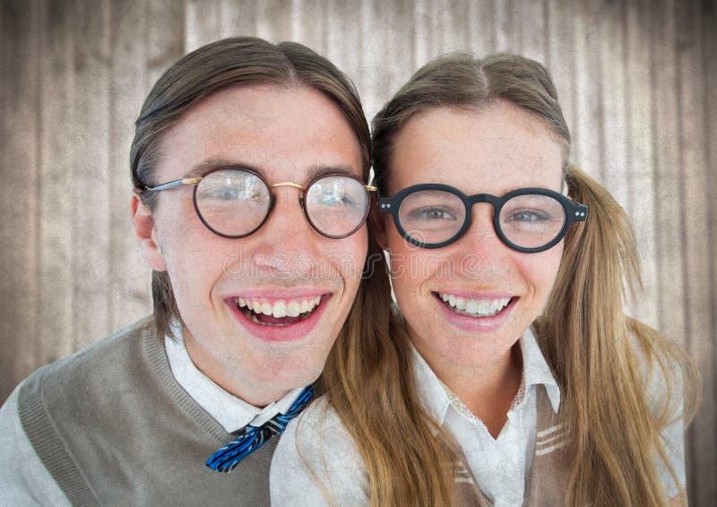 Sluit omhoog van nerdpaar tegen onscherp houten paneel met grungebekleding stock afbeeldingen