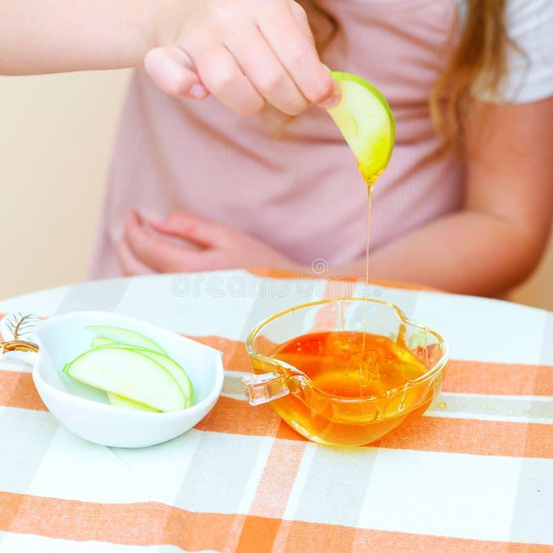 Sluit omhoog van onderdompelende de appelplakken van het handen Joodse kind in honing op Rosh Hashanah royalty-vrije stock foto