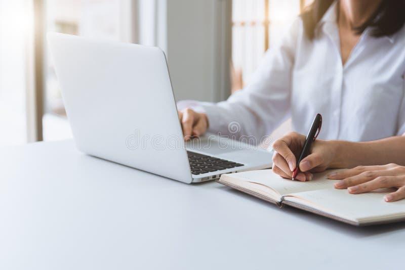 Sluit omhoog van onderneemster twee gebruikend laptop en schrijvend op notitieboekje in de ochtend Zaken en financieel concept Me royalty-vrije stock foto's