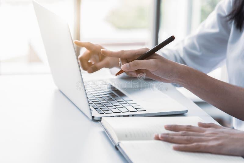 Sluit omhoog van onderneemster twee gebruikend laptop en schrijvend op notitieboekje in de ochtend Zaken en financieel concept Me stock afbeelding