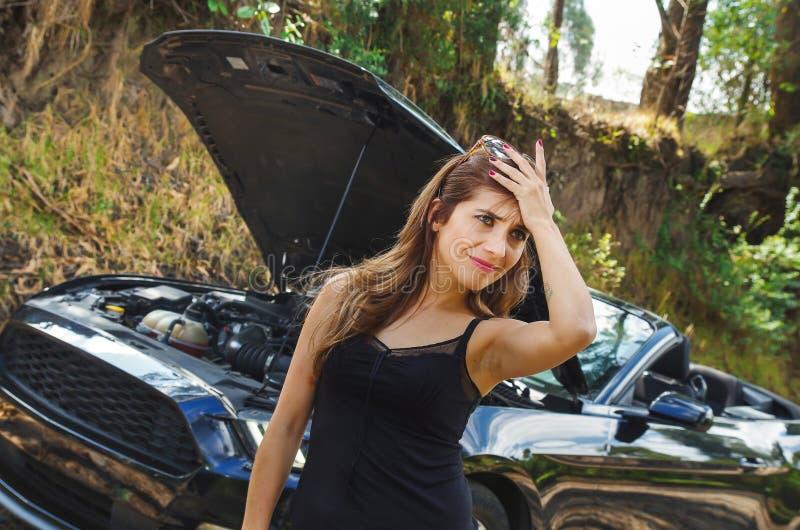 Sluit omhoog van ongerust gemaakte vrouw die sunglases in haar hoofd, zwarte t-shirt en jeans dragen, die een probleem met zwarte royalty-vrije stock fotografie