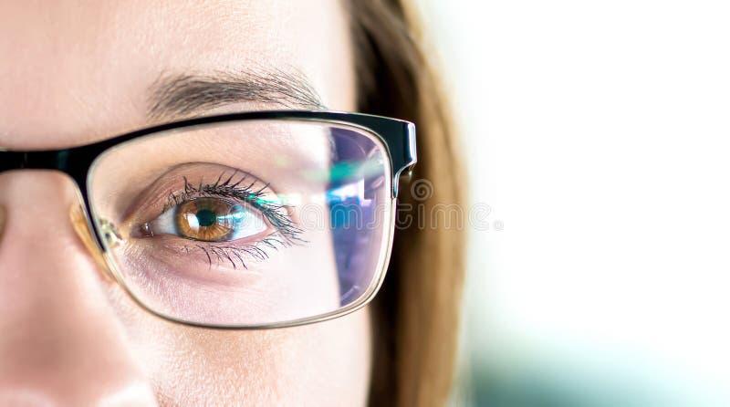 Sluit omhoog van oog en vrouw die glazen dragen Optometrie, bijziendheid of het concept van de laserchirurgie Bruin eyed meisje m royalty-vrije stock afbeelding