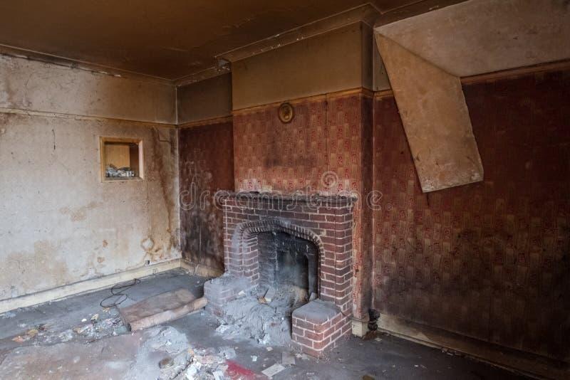 Sluit omhoog van open haard in verlaten huis, met behangschil van de muur Eg het UK stock foto