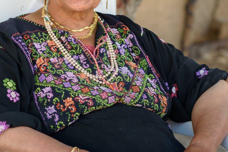 Sluit omhoog van oude Arabische vrouw met traditionele Arabische kledingszitting op stoel stock fotografie