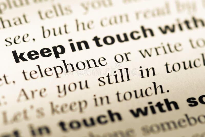 Sluit omhoog van oude Engelse woordenboekpagina met woord in contact blijven met stock afbeelding