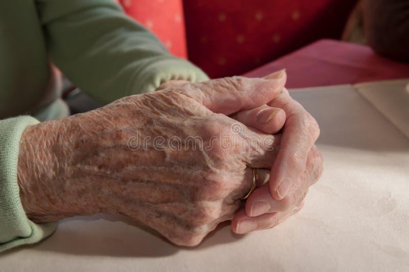 Sluit omhoog van oude gevouwen handen van hogere vrouw royalty-vrije stock afbeeldingen