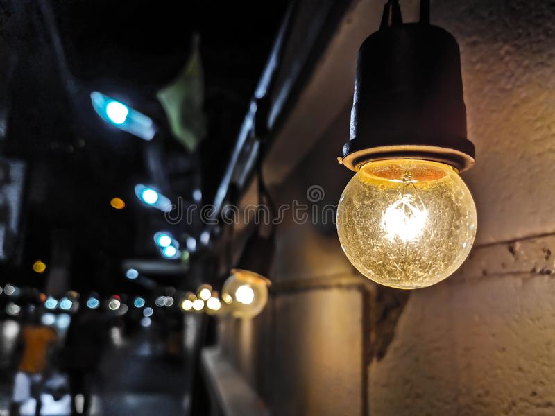 Sluit omhoog van oude ronde gloeilampen naast de concrete muur bij nacht in Bangkok, Thailand op vage bokek achtergrond Licht van royalty-vrije stock afbeelding