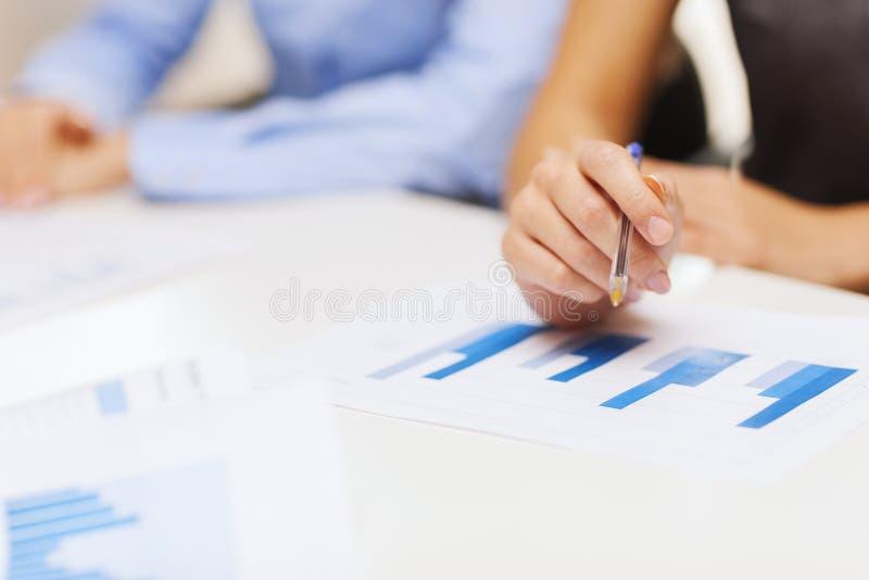Sluit omhoog van praatjes en grafieken in bureau stock afbeelding