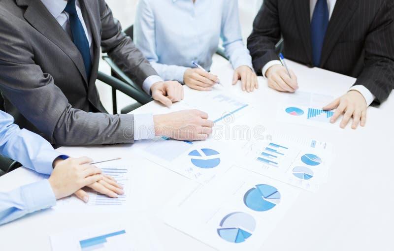 Sluit omhoog van praatjes en grafieken in bureau royalty-vrije stock afbeeldingen