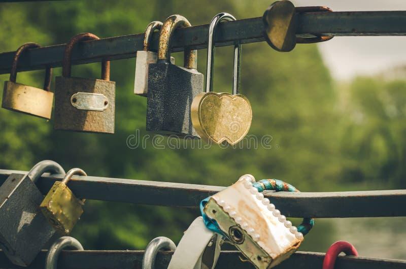 Sluit omhoog van rij van liefdesloten/Minnaarsleutels voor belofte op brug royalty-vrije stock afbeelding