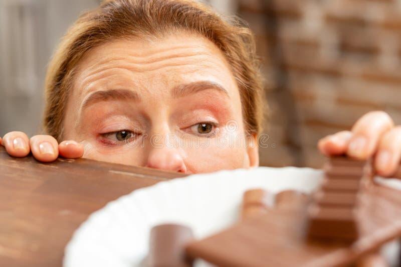 Sluit omhoog van rijpe vrouw met hypergevoeligheid die chocolade nemen royalty-vrije stock foto