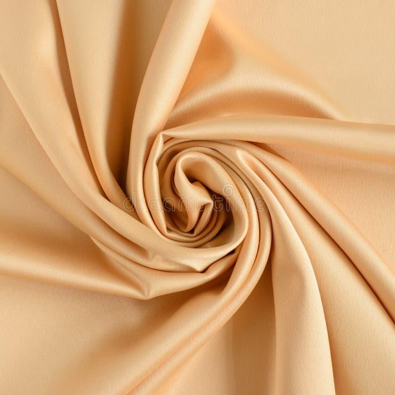 Sluit omhoog van rimpelingen in vorm van roze bloem in goud gekleurde zijdestof Satijn textielachtergrond stock foto's