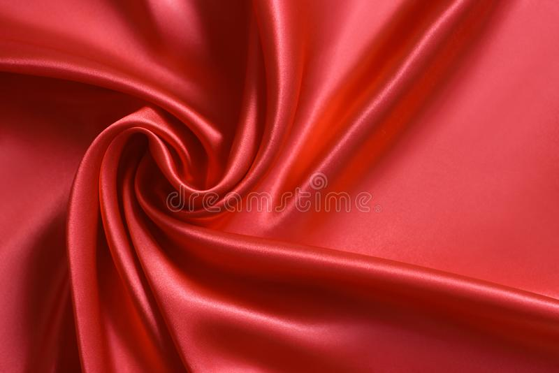 Sluit omhoog van rimpelingen in vorm van roze bloem op rode zijdestof Satijn textielachtergrond royalty-vrije stock foto